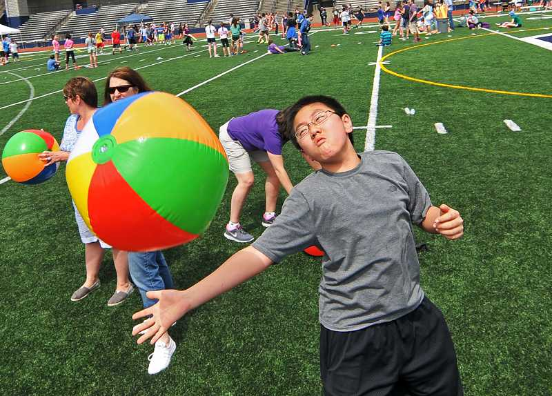 by: REVIEW PHOTO: VERN UYETAKE - Max Chu, seventh grade, bats a beach ball as groups compete to keep the ball in the air as long as they can.