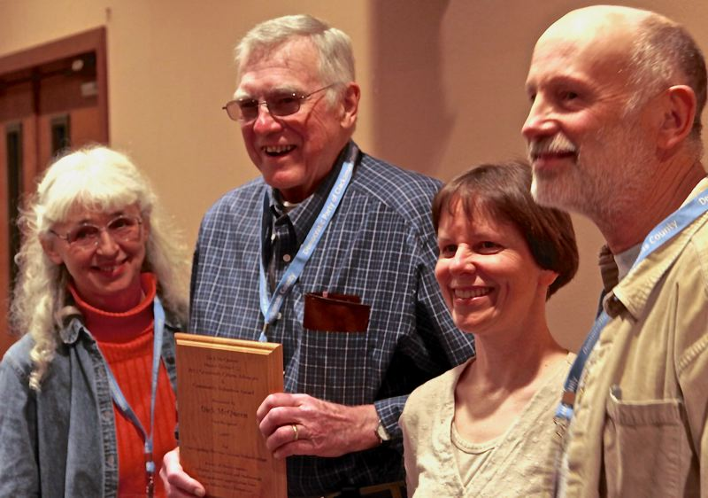 by: CONTRIBUTED PHOTO: SANNYE PHILLIPS - Pictured immediately after the first presentation of the Dick McQueen Award are, from left, Susan Drew, co-district leader of the Oregon Democrats in Clackamas County House District 52; McQueen holding the award; Stephanie Nystrom, district leader of Oregon Democrats in Multnomah County HD-52; and Dennis Ghelfi, co-district leader of Oregon Democrats in Clackamas County HD-52.
