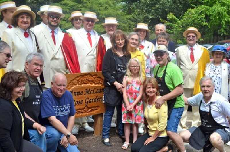 by: MIKE WATTERS - Participants at Century Garden Day gather around the Anne McLean Rose Garden sign.