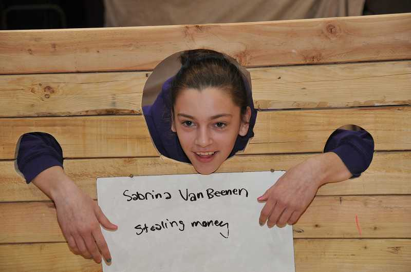 by: VERN UYETAKE - Sabrina VanBeenen, sixth grade, gets her picture taken in the stocks at the Rosemont Ridge Middle School Renaissance Faire.