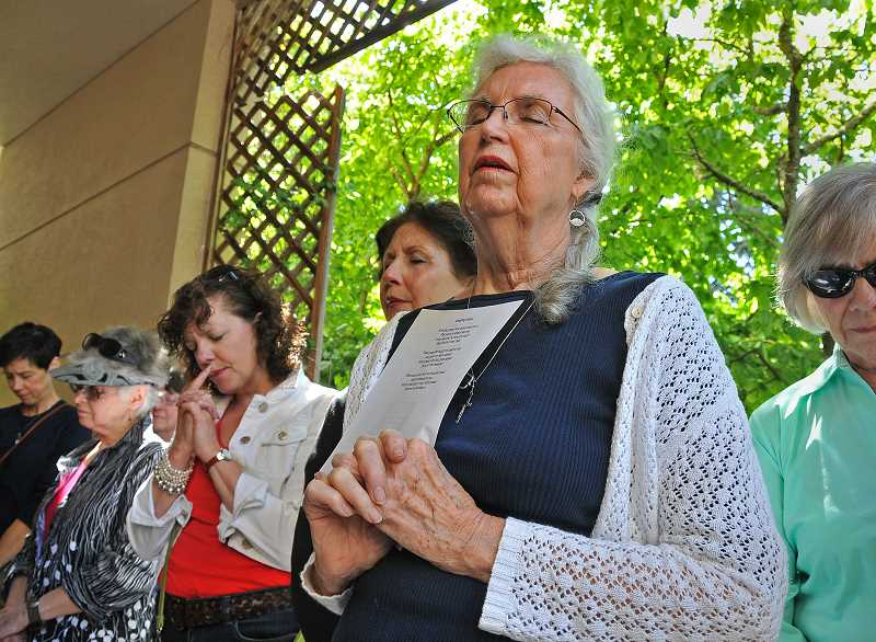 by: VERN UYETAKE - Barbara Morejohn of Lake Oswego closes her eyes in prayer at the National Day of Prayer in Lake Oswego last Thursday.