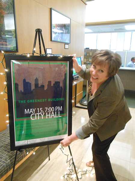 by: CLIFF NEWELL - Diana Smith-Bouwer prepares her marquee for the film 'The Greenest Building,' which will be shown in Lake Oswego on Wednesday.