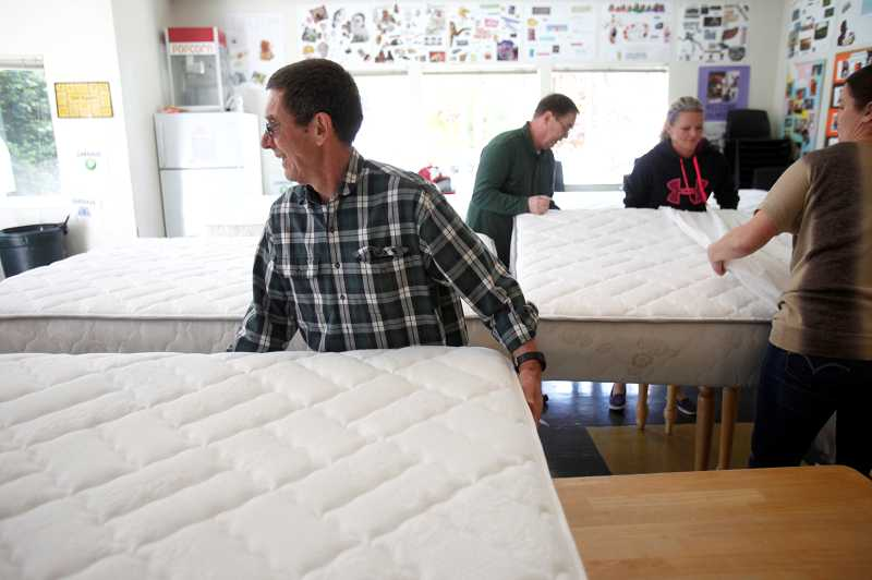 by: TIMES PHOTO: JONATHAN HOUSE - Lynn Vancil, left, and many volunteers helped bring in new mattresses to the Good Neighbor Center in Tigard. Local Sealy stores donated the mattresses to organizations across the region.