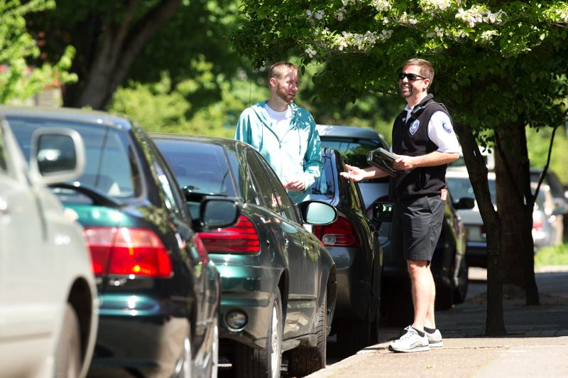 by: TRIBUNE PHOTO: CHRISTOPHER ONSTOTT - Parking inspector john Buechler explains the new Northwest Portland permit parking rules to a resident on Northwest Irving Street. Over 2,600 $60 permits have been bought by residents and shop owners in the neighborhood.