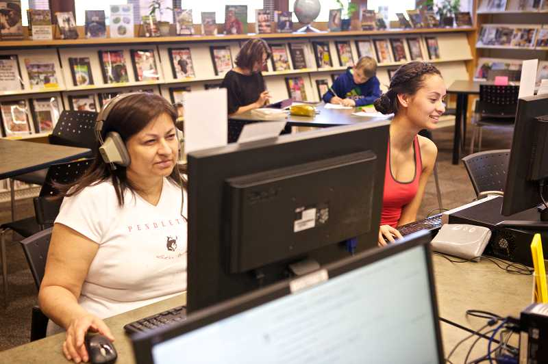 by: TIMES PHOTO: JAIME VALDEZ - Bertha Arellano and her daughter, Maira Garcia, 19, a senior at Southridge High School, search websites on the computers at the Beaverton City Library's Murray-Scholls Branch.