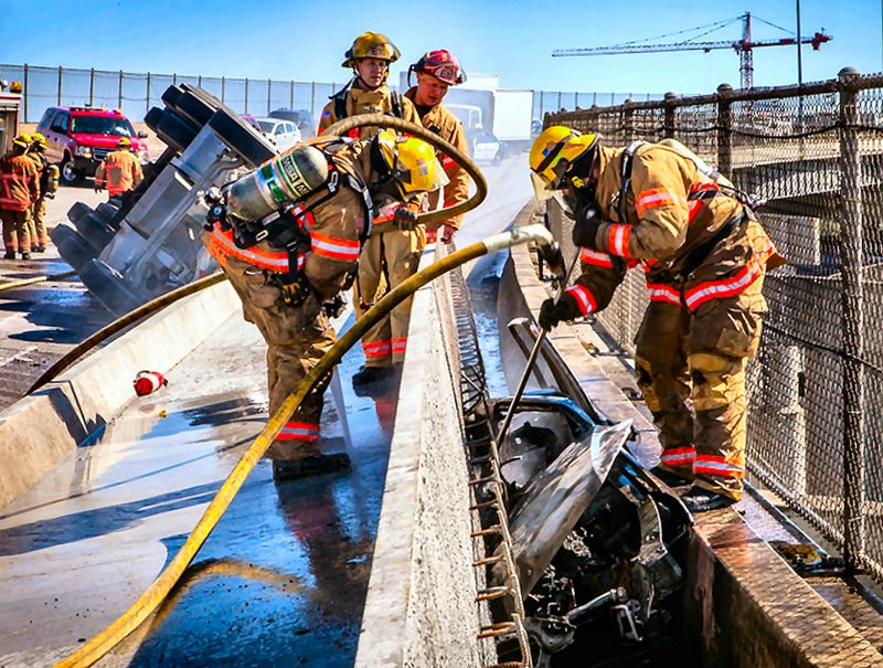 by: GREG MUHR, PF&R - Firefighters made sure the car fire was completely extinguished. That bit of metal protruding from the beam at lower right is about all thats left of the crushed car.