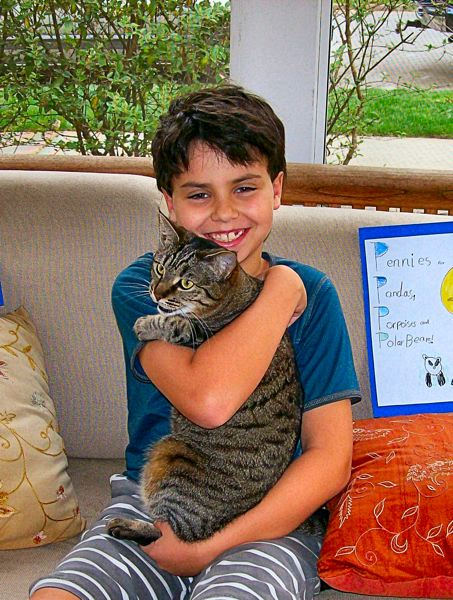 by: RITA A. LEONARD - Duniway student Henry Matusow, with his cat, Luna. The third grader raised a total of $2,823.74 to help preserve wildlife habitats.
