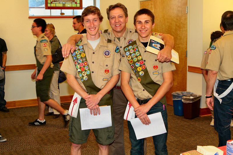 by: DAVID F. ASHTON - Troop 64 Scoutmaster Jim Sharp congratulates the two new Eagle Scouts who flank him: Collin Faunt and Kevin Craig.