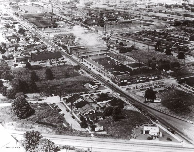 by: COURTESY OF THE PECO COMPANY - This photo is an aerial view of the business district on 17th Avenue between McLoughlin and Holgate around 1935, just before the PECO manufacturing structure was built. The Iron Man Manufacturing Company is present in the photo - as is the now-gone Brooklyn Yard Roundouse, in the upper left corner, near Holgate Boulevard.