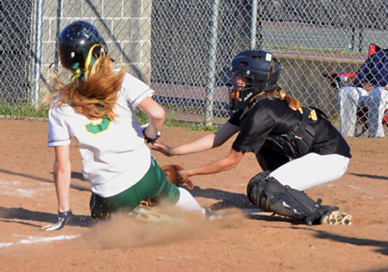 by: JOHN BREWINGTON - St. Helens' Michelle Sass tags out Rex Putnam runner to preserve shut-out during game this past week.