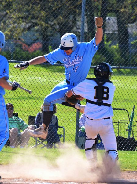 by: JOHN BREWINGTON - St. Helens catcher Bryce Winnier tags out a leaping Kevin Lave of Liberty last week during a three-game series between the two teams. St. Helens won the last game of the series to break a nine-game losing streak.