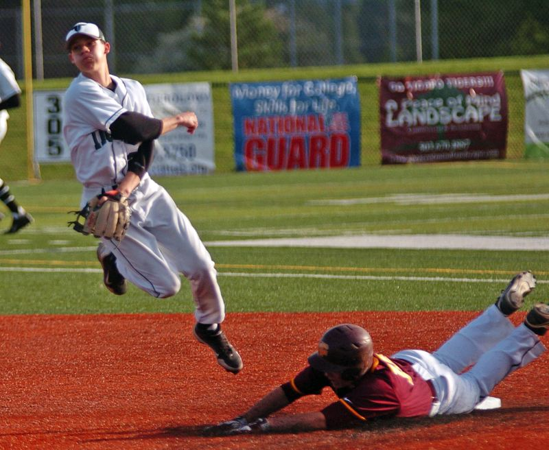 by: DAN BROOD - MAKING THE TURN -- Tigard High School junior shortstop Shane Rasor (left) makes a throw to first after forcing Forest Grove's Dylan Haugen at second base in last week's game.