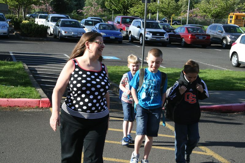 by: CONTRIBUTED PHOTO: OSEA - Sue Mutschler fills in as crossing guard, helping students, from left, Austin and Tyler Redford and Graham Arnold cross to Woodland Elementary School.