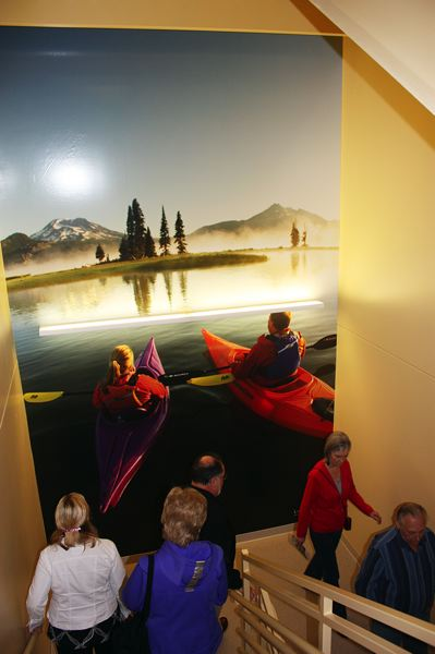 by: HILLSBORO TRIBUNE PHOTO BY DOUG BURKHARDT - Colorful murals in the usually drab and unappealing stairwells are designed to encourage people to use the stairs, saving energy and helping people get a bit more exercise. This image of two kayakers was created by Lance Koudele of Hood River.