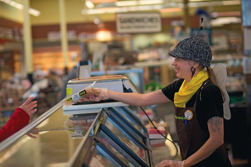 by: PAMPLIN MEDIA GROUP: CHRISTOPHER ONSTOTT - Katie Passero dresses as a bee to work the counter at New Seasons Market, as part of the companys Bee Part of the Solution campaign.