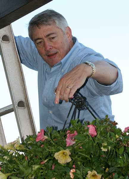 by: FILE PHOTO - The Rev. Keith Dickerson has become an expert at hanging flower baskets in his five years as director of the Lake Oswego Chamber of Commerce flower basket program.