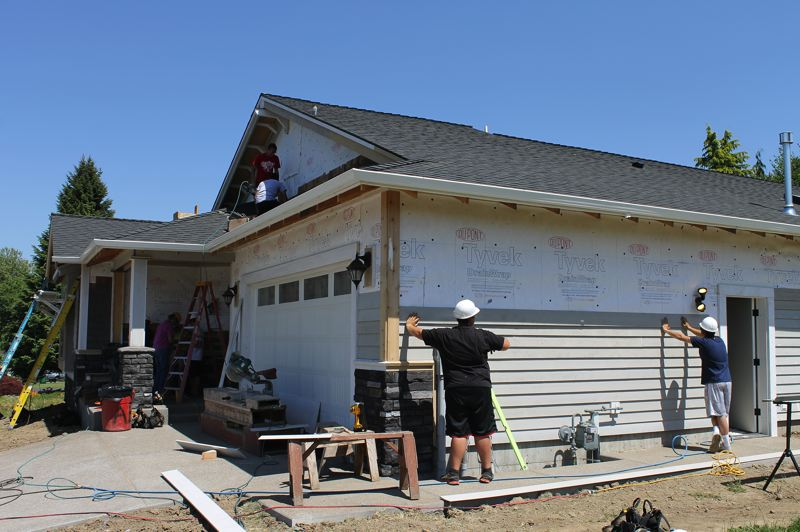 by: NEWS-TIMES PHOTO: JOHN SCHRAG - Forest Grove High School students work hard to put the finishing touches on the exterior of the 2013 Viking House, located on Windstream Street.