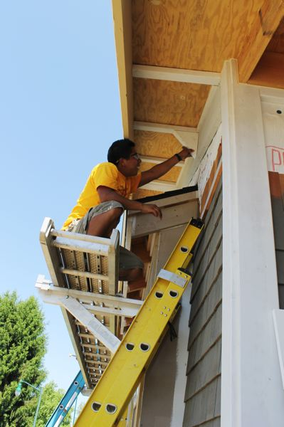 by: NEWS-TIMES PHOTO: JOHN SCHRAG - Jose Perucho installs a decorative brace to a front gable on the Viking House.
