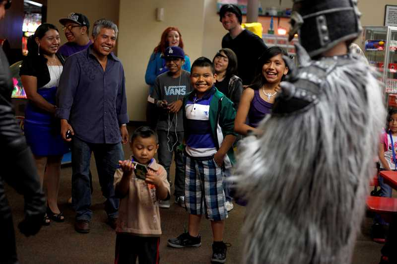 by: TIMES PHOTO: JONATHAN HOUSE - Bryan Dolores-Cruz, center, along with friends and family, is greeted by invading aliens at Laserport in Beaverton, during his Make-A-Wish adventure featuring characters from his favorite cartoon show, 'Ben 10.'