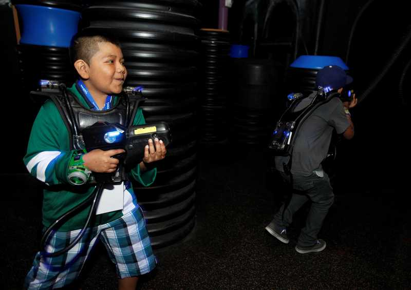 by: TIMES PHOTO: JONATHAN HOUSE - Bryan Dolores-Cruz hunts villians from his favorite cartoon show, 'Ben 10,' during a game of laser tag.