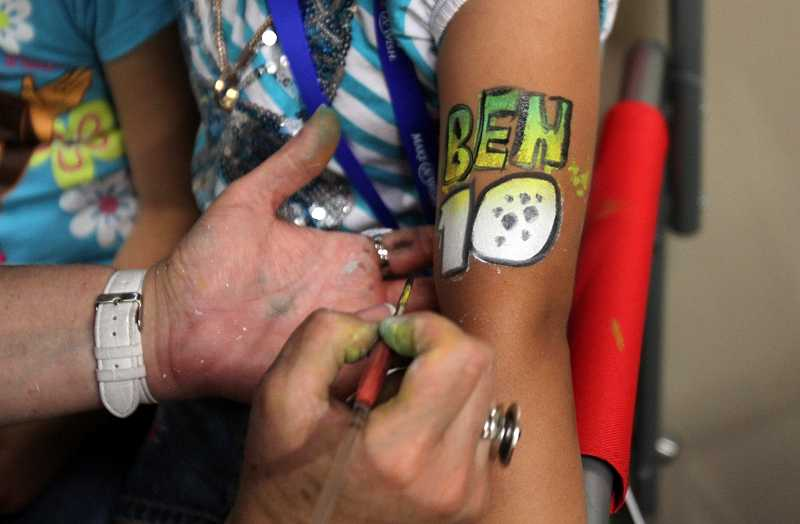 by: TIMES PHOTO: JONATHAN HOUSE - An artist was on hand to give temporary 'Ben 10' tattoos during Bryan Dolores-Cruzs Make-A-Wish party at Laserport.