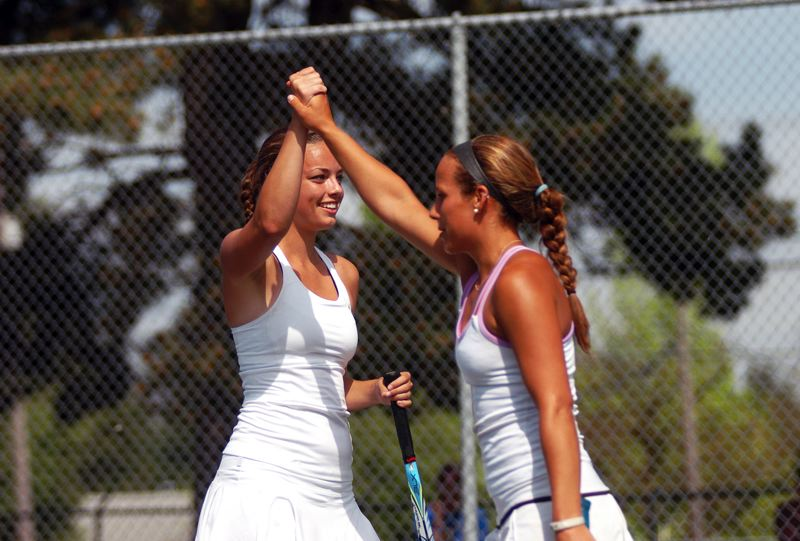 by: DAN BROOD - TUALATIN TEAMWORK -- Tualatin High School seniors Eloise Loen (left) and Mollie Freel celebrate after scoring a point in the girls doubles championship match of the Pacific Conference district tennis tournament on Saturday.