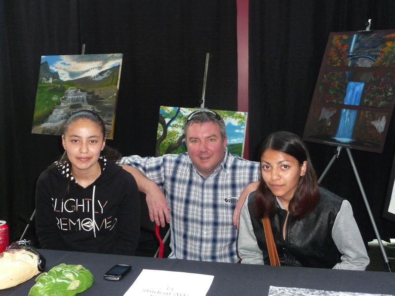 by: COURTESY PHOTO: BRIAN BUCKNER - Canda Zavala-Juarez and Yetlanezi Zaval-Juarez pose with Liberty social studies teacher Brian Buckner last Saturday at the Memorial Coliseum. The sisters both had their artwork on display as a part of the Dalai Lamas visit to Portland.