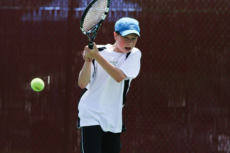 by: HILLSBORO TRIBUNE PHOTO: AMANDA MILES - Century freshman Tommy Edwards hits a backhand during his two-set victory over Newberg's Anthony Croteau in the finals of the district tennis tournament.