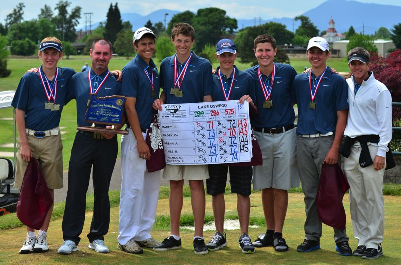 The Lake Oswego varsity boys golf team and coach Jason Owens, stand with their medals, team trophy and score sheet at Trysting Tree in Corvallis following the team's state championship showing. The Lakers shot -1 as a team and won by 10 strokes.