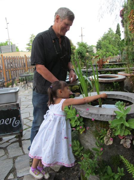 by: PHOTO: DICK TRTEK - Phil Yates shows Yuna, 4, how to feed the fish in one of his wicking wells, behind Singer Hill Cafe.