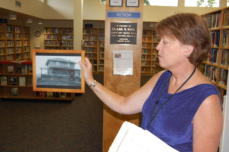 by: PHOTO BY: RAYMOND RENDLEMAN - Katie Newell, director of Milwaukie's Ledding Library hold a photo of Florence Ledding's house, parts of which are still standing within the city library that was built over the house in 1964.