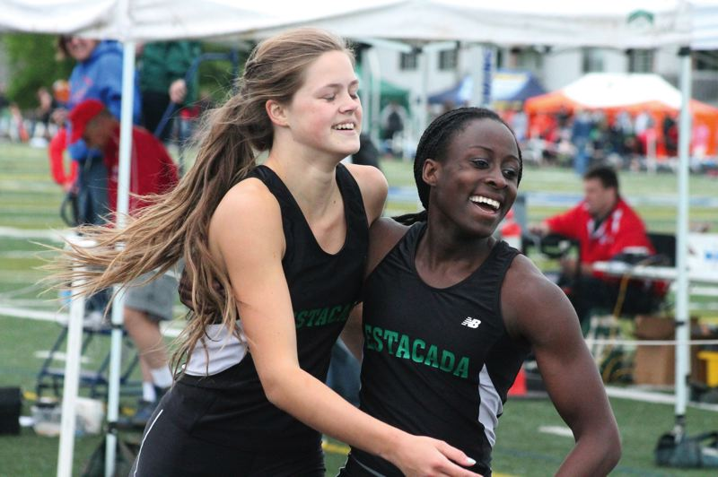 by: PAMPLIN MEDIA GROUP: COLIN STORM - Estacada teammates Tori Johnson, left, and Genna Settle celebrate after finishing 1-2 in the 200-meter final.