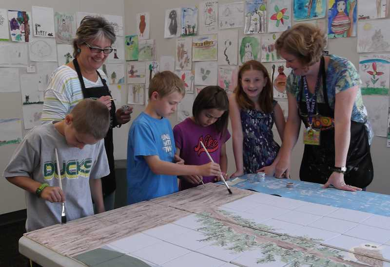 by: KATE HOOTS - Trillium fourth-graders, from  left, Caden Parker, Zack Scott, Ava Peters and Nicole Brunette,  work on May 3 with Maggie Englund, left, and Joan Carlson, on a mural that will be installed in the schools lobby.