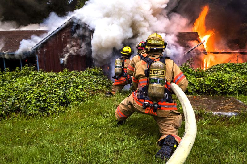 by: CONTRIBUTED PHOTO: GREG MUHR - Firefighters fight back the flames at a residetial fire that claimed the life of Troutdale resident Donald Krebs, 87.