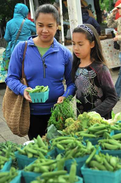 by: VERN UYETAKE - Jovi Fairchild and her daughter, Sophia Bradley, 8, peruse a bounty of fresh vegetables at the Lake Oswego Farmers' Market on Saturday.
