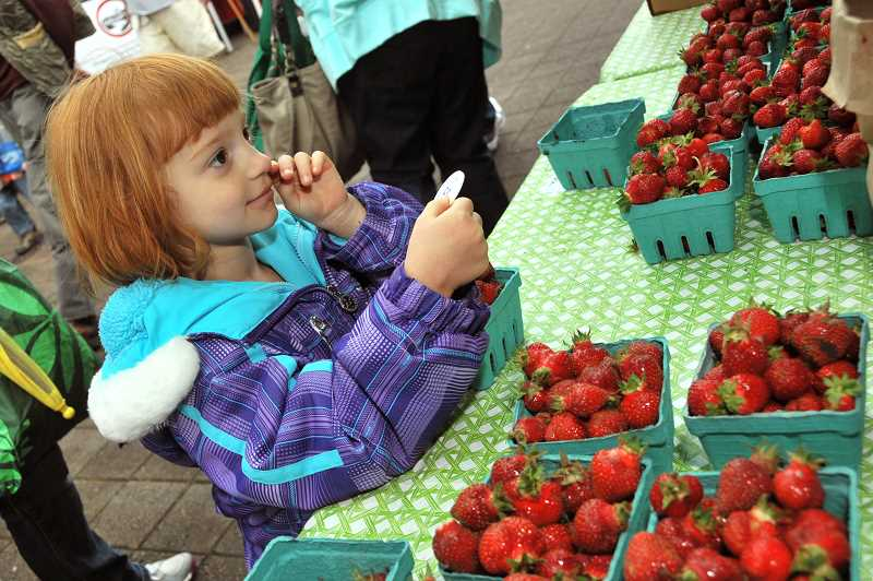 by: VERN UYETAKE - Strawberries, strawberries everywhere were encountered by Violet Rike of Lake Oswego. Despite some rainfall, a crowd estimated at 7,500 people showed up for the first market of the year. 'We had a wonderful opening day,' said Jamie Inglis, market manager.