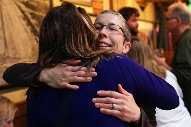 by: TIMES PHOTO: JAIME VALDEZ - Parent-volunteer Karyn Servin hugs Amy Davis, another parent-volunteer, after learning Tuesday night that voters approved the Beaverton School District's local-option levy.