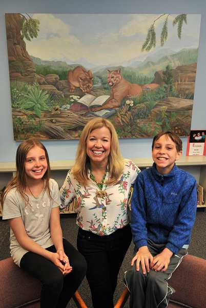 by: REVIEW PHOTO: VERN UYETAKE - Lake Grove parent Keri Bloom poses with her twins, Arielle and Max, in the school library with her painting of cougars reading.