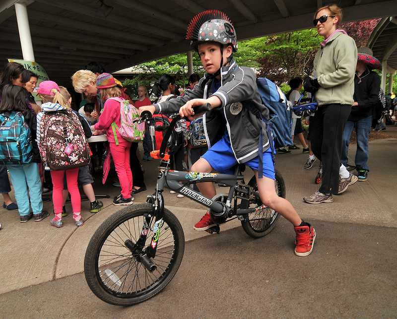 by: REVIEW PHOTO: VERN UYETAKE - Lake Grove third-grader Finn McAuley rides his bike in style to school.