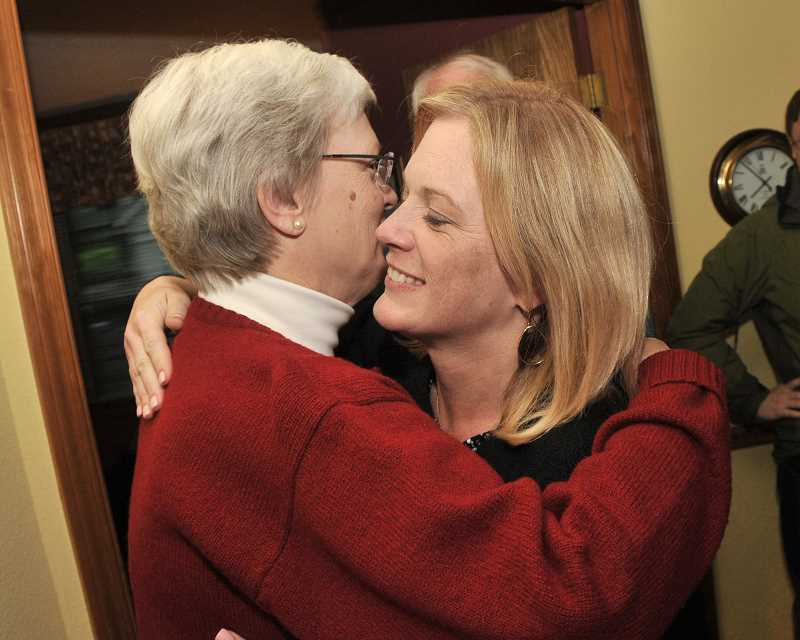 by: VERN UYETAKE - School board candidate Sarah Howell receives a hug from her mother, Carolyn Wiecks, as congratulations for running a strong campaign at an election night party Tuesday in Lake Oswego. Howell was leading in the race for Position 2 at the time.