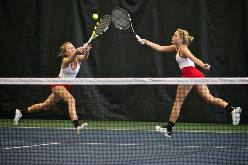 by: TRIBUNE PHOTO: JAIME VALDEZ - Lincoln Highs Allie Hueffner (left) and Kadie Hueffner go for a ball in their states doubles final last Saturday against Jesuits Darby Rosette and Sarah Murphy at Tualatin Hills Tennis Center. The Hueffner twins won 6-2, 6-3 to propel the Cardinals to the Class 6A championship by one point over Jesuit. The teams tied last year, and Lincoln took the crown in 2009 and 2010. The Hueffners also won the doubles title in 2012.