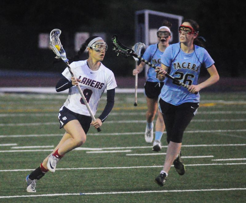 by: MATTHEW SHERMAN - Lake Oswego's Zoe Wong looks to get past Lakeridge's Maddie Hearn during the Lakers' playoff win last week.
