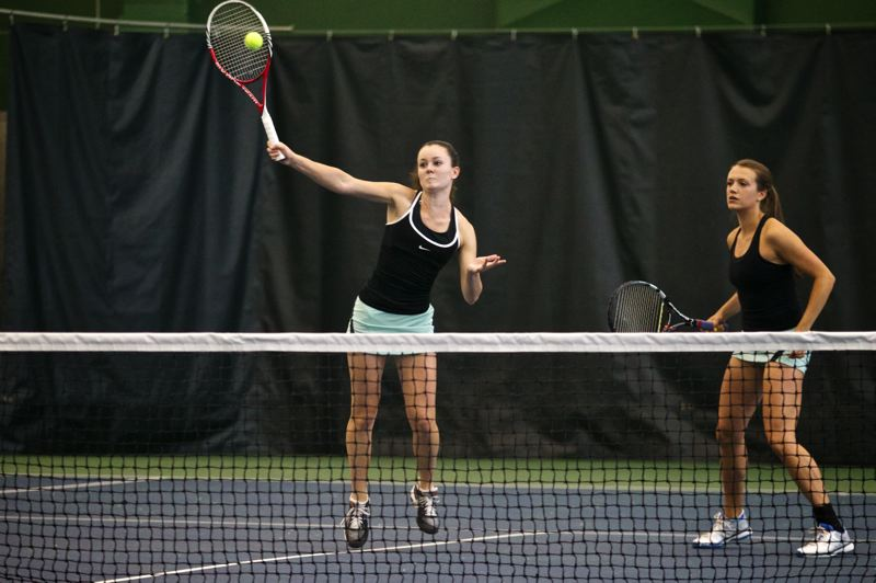 by: TIMES PHOTO: JAIME VALDEZ  - Jesuit Crusaders Sarah Murphy comes to the net as doubles partner Darby Rosette watches in the 6A girls doubles tennis  championships against Lincoln senior twin sisters, Kadie and Allie Hueffner, at Tualatin Hills Tennis Center.