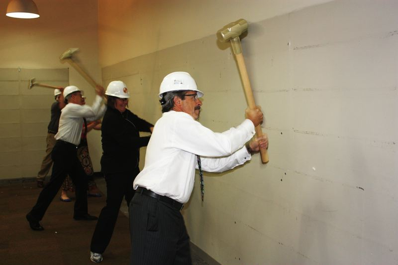 by: HILLSBORO TRIBUNE PHOTO: DOUG BURKHARDT - Looks like asbestos, Mayor Jerry Willey jokes with the crowd after taking a ceremonial first swing with a golden sledgehammer at Hillsboros Shute Park Library last Friday. The library is being almost completely rebuilt in a project that will keep the facility closed until March 2014.