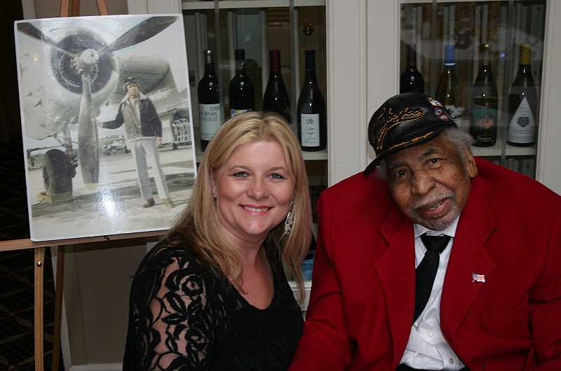 by: SUBMITTED - Ben Flaps Berry of the immortal Tuskegee Airmen was greeted by Melody Buenger at the Tribute to Heroes. At the left is a photo of Berry as a young pilot.