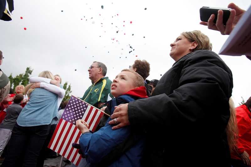 by: TIMES PHOTO: JONATHAN HOUSE - Braxton Alverts and his mother Michelle watch as hundreds of balloons with messages for Andrew Keller are released into the air during a Memorial Day ceremony in Southwest Beaverton.