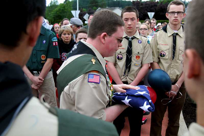 by: TIMES PHOTO: JONATHAN HOUSE - Southridge High School sophomore Thomas Grooms holds an American Flag as he makes his way to a waiting military honor guard at the newly installed flag pole at the Andrew Keller Memorial Circle that he helped create as part of his Eagle Scout project.