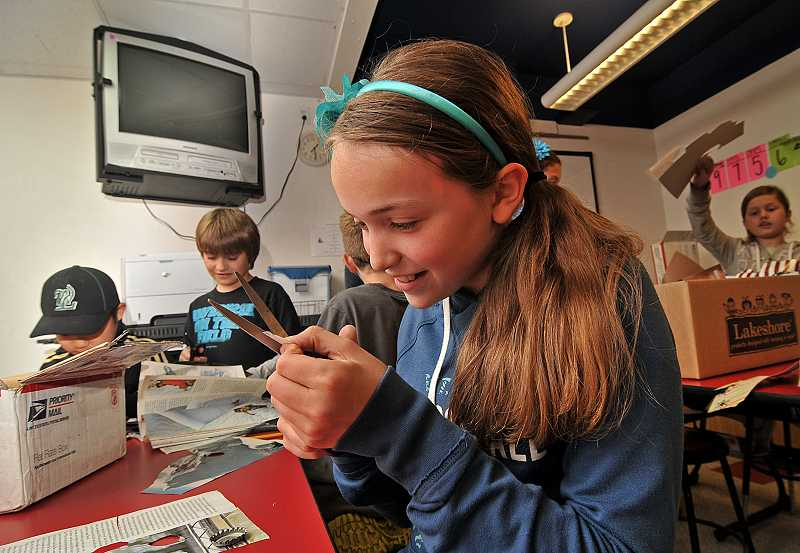 by: SPOKESMAN PHOTO: VERY UYETAKE - Emma Fulmer works on a bottle cap design.