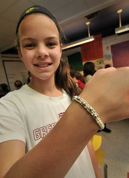 by: SPOKESMAN PHOTO: VERY UYETAKE - Carey Stell models one of the bracelets the class made to sell.