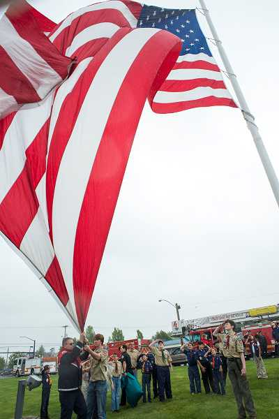 by: NEWS-TIMES PHOTO: CHASE ALLGOOD - Forest Groves large ceremonial flag is hoisted into place Monday by local firefighters and Boy Scouts. Delegates to the Scouts national convention voted May 23 to admit openly gay youth to the century-old organization.